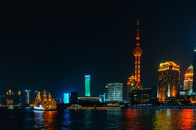 Shanghai skyline at night with traditional sail boat