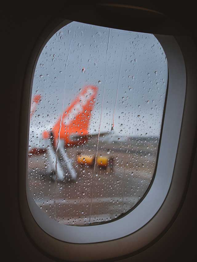 Aeroplane window on a rainy day looking towards easyjet plane