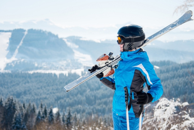 Lady with ski clothes and equipment looking out towards mountains