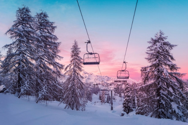 Ski lifts in front of the sunset